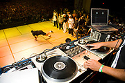 One dancer performing on stage and other team members cheering for him and DJ decks in the foreground. UK B-Boy championships 06. 08/10/2006