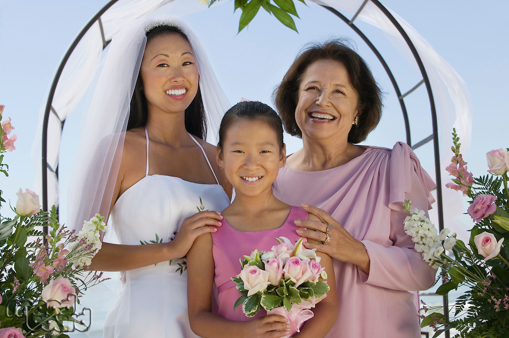 Bride with mother and sister outdoors (portrait)