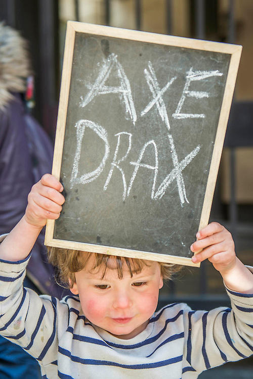 Arthur, aged three, makes his feelings known with his toys (T-rex and black board) and his mother - #AxeDrax protest outside the annual Drax shareholder AGM. Protestors demanded cleaner, greener energy generation systems. They continued on to the Department of Energy and Climate Change to deliver a petition demanding that subsidies given to Drax, for burning biomass, be stopped for making climate change worse.