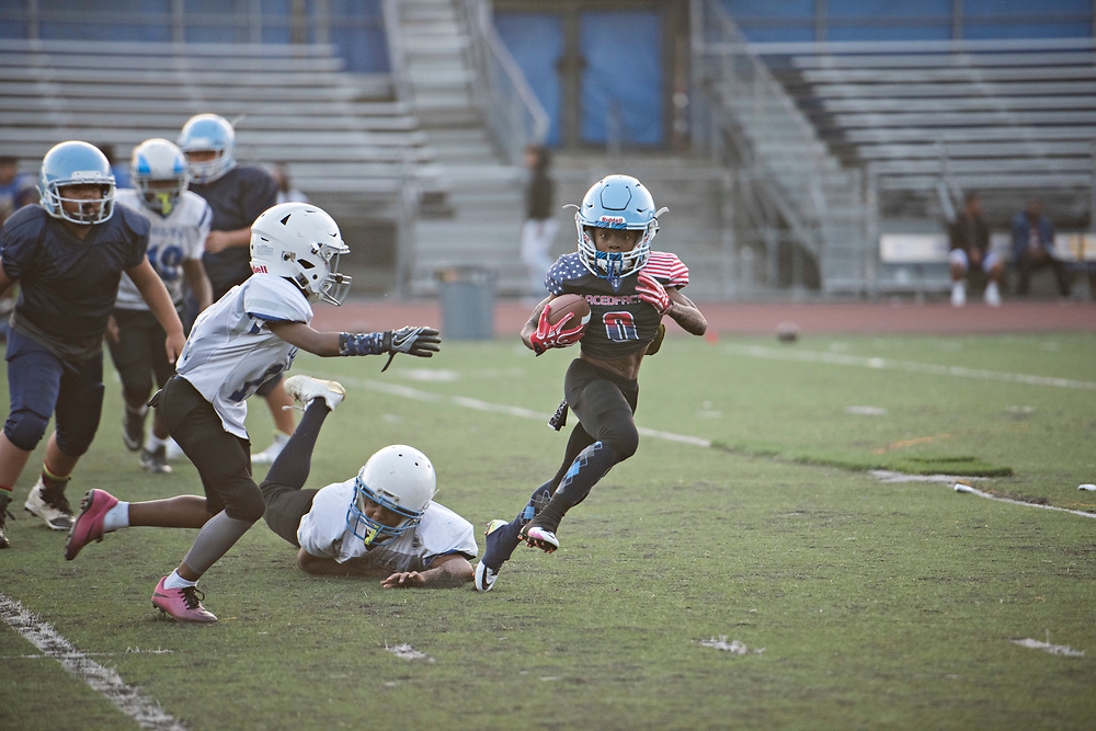 "During a scrimmage against the Compton Colts, the quarterback of the Hub City TarHeels hands off to Maxwell ""Bunchie"" Young, 10, who's known for his blazing speed and his ability to make plays."