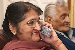 Elderly south Asian couple, woman on phone.