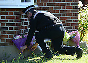 © Licensed to London News Pictures. 07/09/2012. Claygate, UK A policeman places flowers given by a neighbour. The family home of Saad al-Hilli in Claygate, near Esher. Three members ofof the family have been shot dead in the French Alps. Photo credit : Stephen Simpson/LNP