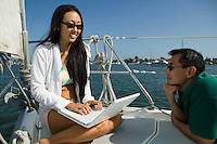Man and Woman Using Laptop on Sailboat
