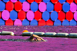 """A swimmer at the lido in Hyde Park swims past Christo's """"Mastaba"""" art installation floating on The Serpentine as another heatwave day begins with temperatures expected to soar. London, July 01 2018."""