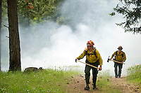 Idaho Department of Lands firefighters Adam Furlin, left, and Mykel Guidry hike up a Patzer Peak to an area set on fire for a wildfire  training session.