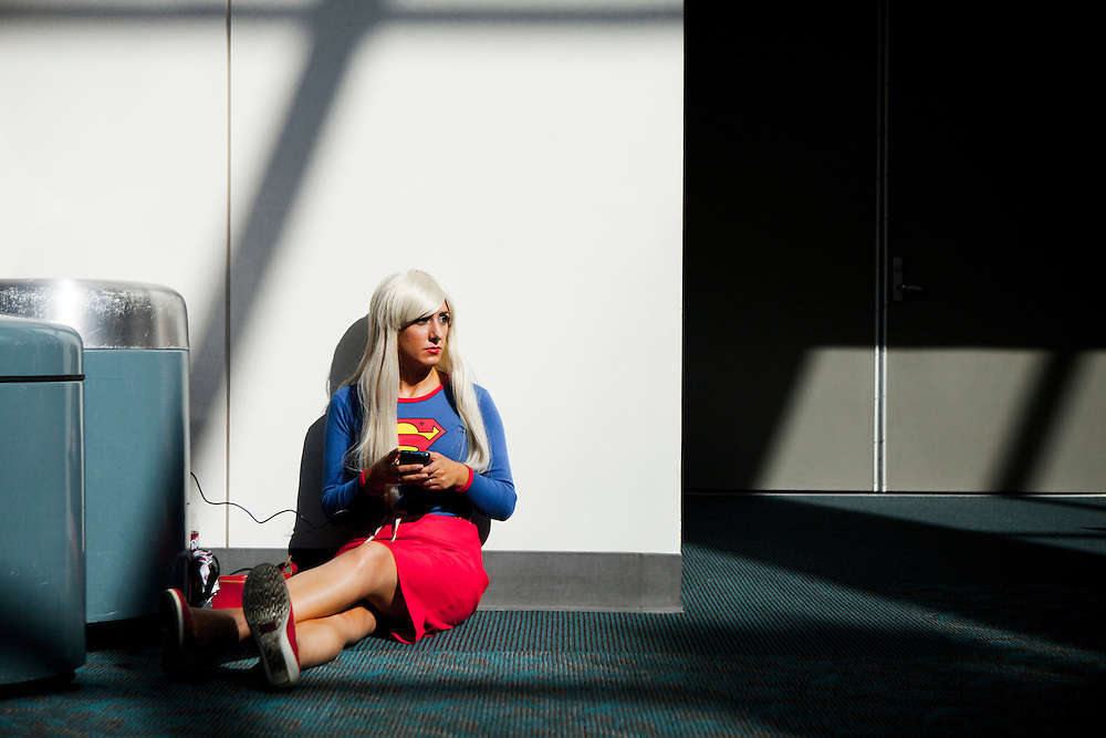 Super Girl takes a break from saving the world to charge her cellphone.