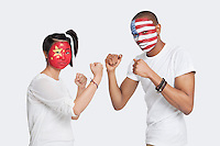 Portrait of young man and woman with national flags painted on face holding up their fists to fight against white background