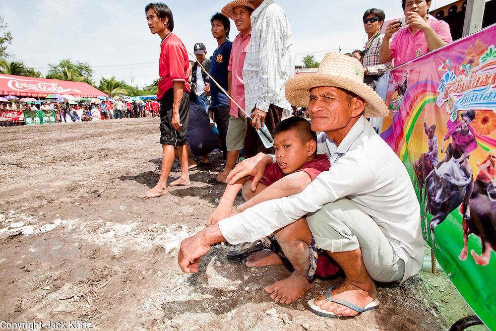 Oct. 3, 2009 - CHONBURI, THAILAND: A man and his son watch the action during the first day of races at the Chonburi Buffalo Races Festival, Saturday, Oct. 3. Contestants race water buffalo about 200 meters down a muddy straight away. The buffalo races in Chonburi first took place in 1912 for Thai King Rama VI. Now the races have evolved into a festival that marks the end of Buddhist Lent and is held on the first full moon of the 11th lunar month (either October or November). Thousands of people come to Chonburi, about 90 minutes from Bangkok, for the races and carnival midway. Photo by Jack Kurtz / ZUMA Press