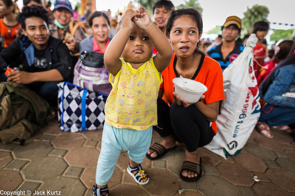 16 JUNE 2014 - ARANYAPRATHET, THAILAND: A Cambodian child and his mother finish their lunch while they wait to be processed by Thai immigration and then returned to Cambodia. More than 150,000 Cambodian migrant workers and their families have left Thailand since June 12. The exodus started when rumors circulated in the Cambodian migrant community that the Thai junta was going to crack down on undocumented workers. About 40,000 Cambodians were expected to return to Cambodia today. The mass exodus has stressed resources on both sides of the Thai/Cambodian border. The Cambodian town of Poipet has been over run with returning migrants. On the Thai side, in Aranyaprathet, the bus and train station has been flooded with Cambodians taking all of their possessions back to Cambodia. PHOTO BY JACK KURTZ