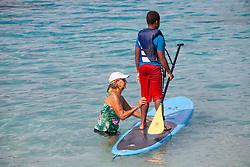 Sally George, left, instructs Jahki Johnson on the paddleboard.  Practicing for Paddle in the Park at Magen's Bay. St. Thomas, USVI.  24 October 2015. © Aisha-Zakiya Boyd