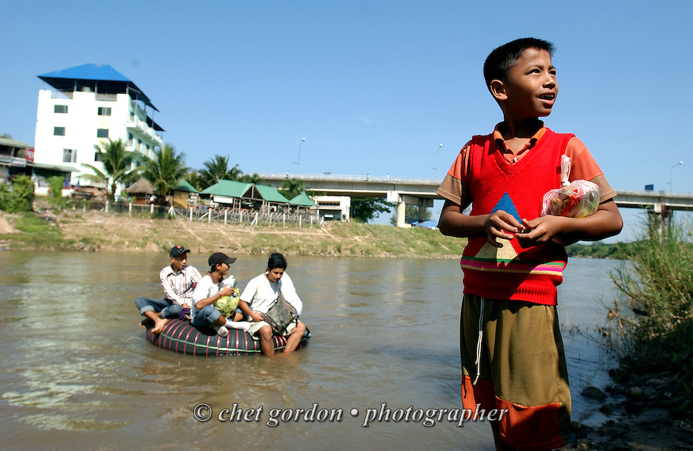 Burmese passengers sit on a rubber raft prior crossing the Moei River from Thailand to Myanmar (Burma) on the banks of the Moei River in Mae Moei City, Thailand on Saturday, November 10, 2007.  © Chet Gordon / THE IMAGE WORKS