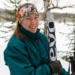 A woman wih her skis in Maine's Katahdin Woods and Waters National Monument. East Branch of the Penobscot River is in the background.