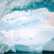 A large hole carved out of an Antarctic iceberg, with a second large iceberg visible through the hole. Curtis Bay, Antarctica.
