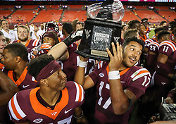 Sep 3, 2017; Landover, MD, USA; Virginia Tech Hokies quarterback Josh Jackson (17) holds the Black Diamond Championship trophy after beating the West Virginia Mountaineers at FedEx Field. Mandatory Credit: Ben Queen-USA TODAY Sports