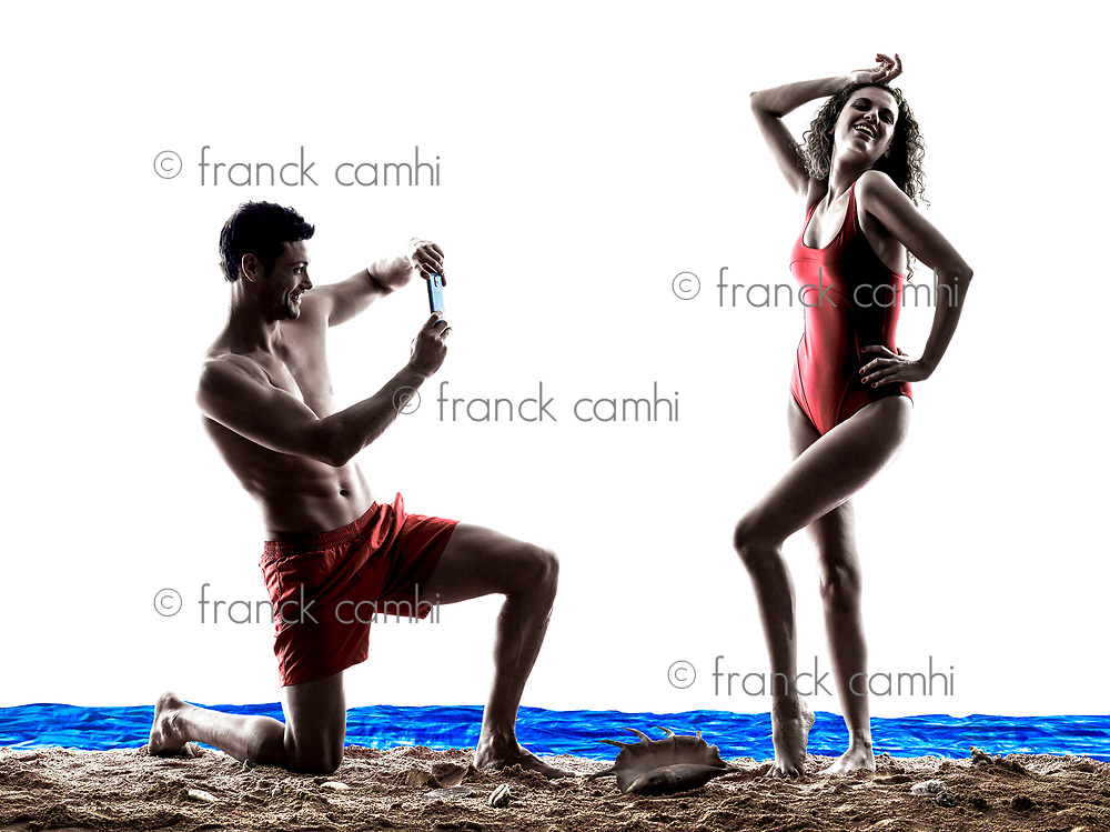 one caucasian couple man and woman photographing selfie on the beach silhouette isolated on white background