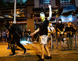 Hong Kong, China. 9th October 2019. Large peaceful crowd gathered to sing songs at MOStown mall in Ma On Shan in solidarity with several security guards who were arrested by police this week. Later small group of protestors went to nearby Shatin Divisional Police Station and shouted abuse at the police and threw objects. Riot police later charged but no arrests made. Pic; Protestor in police spotlight gestures. Iain Masterton/Alamy Live News.