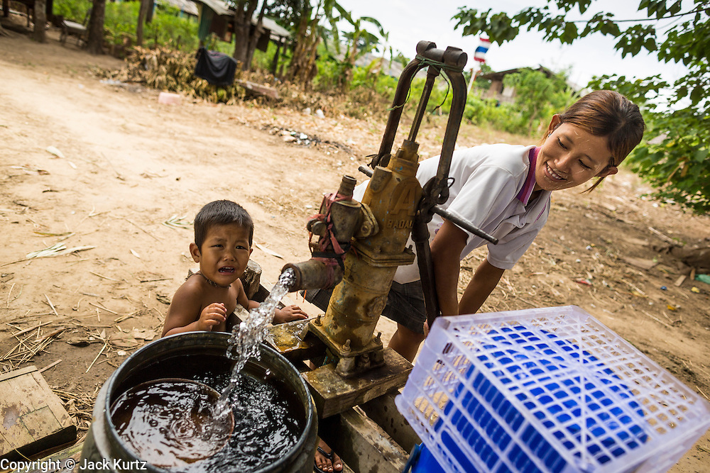 25 MAY 2013 - MAE SOT, TAK, THAILAND:  A Burmese woman and her son pump water from a well in an unofficial village of Burmese refugees north of Mae Sot, Thailand. They live on a narrow strip of land about 200 meters deep and 400 meters long that juts into Thailand. The land is technically Burma but it is on the Thai side of the Moei River, which marks most of the border in this part of Thailand. The refugees, a mix of Buddhists and Christians, settled on the land years ago to avoid strife in Myanmar (Burma). For all practical purposes they live in Thailand. They shop in Thai markets and see their produce to Thai buyers. About 200 people live in thatched huts spread throughout the community. They're close enough to Mae Sot that some can work in town and Burmese merchants from Mae Sot come out to their village to do business with them.   PHOTO BY JACK KURTZ