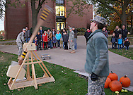 People look on as members of the ROTC launch softballs across the Stewart Memorial Library Quad with a trebuchet at the 11th annual Coe College Playground of Science at Peterson Hall of Science in Cedar Rapids on Thursday, October 24, 2013. Faculty and students from the physics, biology, chemistry, mathematics, computer science, nursing, psychology and ROTC departments provided demonstrations and facilitated hands-on opportunities to show students of all ages that science can be fun.