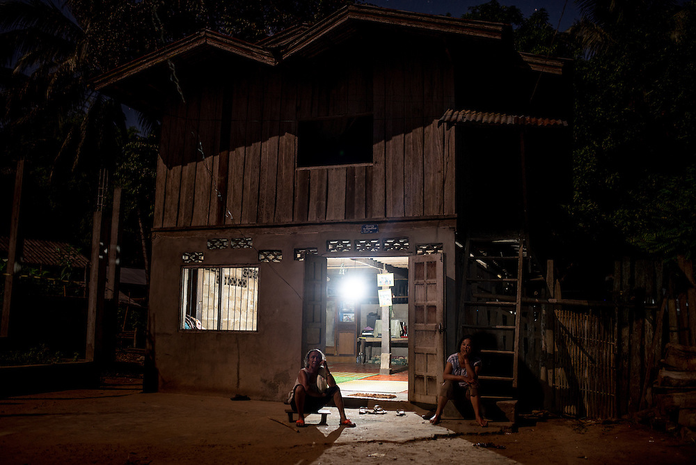A woman sits in front of her home in the village of Khoc Kham. The village is not connected to the main electrical grid and many residents operate their own turbines to power lights and sometimes small appliances.