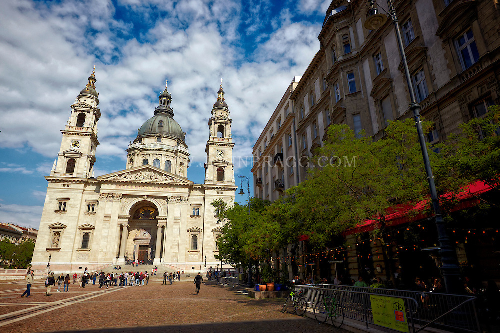 View of Saint Stephens Basilica, tourists, cafe, and cloudy blue skies, Budapest, Germany.
