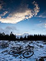 Mountain bike in Heiðmörk forestry area in Reykjavík, Captial of Iceland. Snow on ground and backlight clouds in the sky. Fjallahjól í Heiðmörk að vetri til. Baklýst ský á himni.