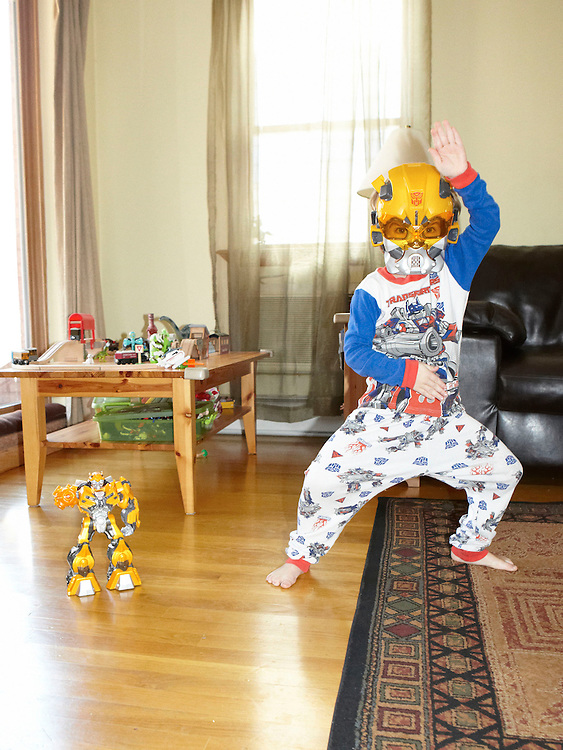 Portrait photograph of child wearing Transformers costume posing next to toy