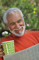 Elderly man reading newspaper outdoors