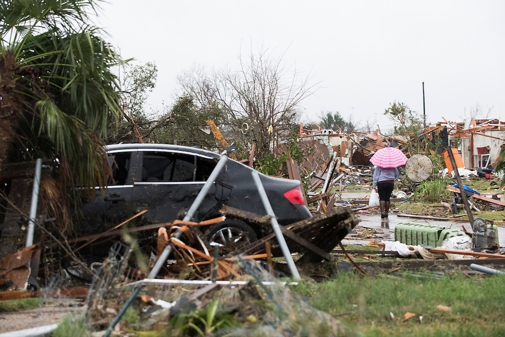 Nery Ceron walks through debris scattered around a neighborhood where homes were hit by a tornado the previous evening in Garland, Texas on December 27, 2015. (Cooper Neill for The New York Times)