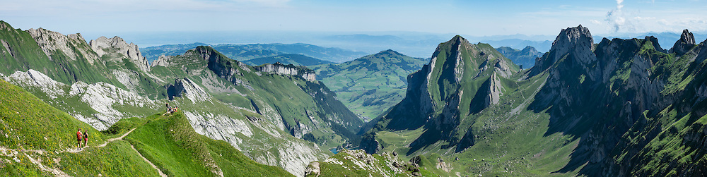 Hikers at Rotsteinpass (2120 m) in the Alpstein limestone mountain range, Appenzell Alps, Switzerland, Europe. Appenzell Innerrhoden is Switzerland's most traditional and smallest-population canton (second smallest by area). This image was stitched from multiple overlapping photos.