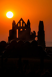 Sunset behind the Gothic ruins of Whitby Abbey overlooking the North Sea on the East Cliff above Whitby in North Yorkshire, England