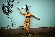 A girl displays her body tattooed in volcanic mud, an ancestral technique, as she poses for a photo aside a stylized graffiti depicting a bird, symbol of the Rapa Nui culture during a festival named Tapati Rapa Nui in Hanga Roa, Rapa Nui, Saturday, Feb. 12, 2011. Boundaries of race become blurrier in the most important Polynesian island, as Chile the country that conquered the territory in the XIX century, tries to push globalization into the island with the same power the Pacific waves reach its rocky shores.