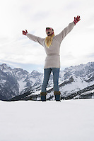 Woman standing on mountain peak with arms outstretched back view