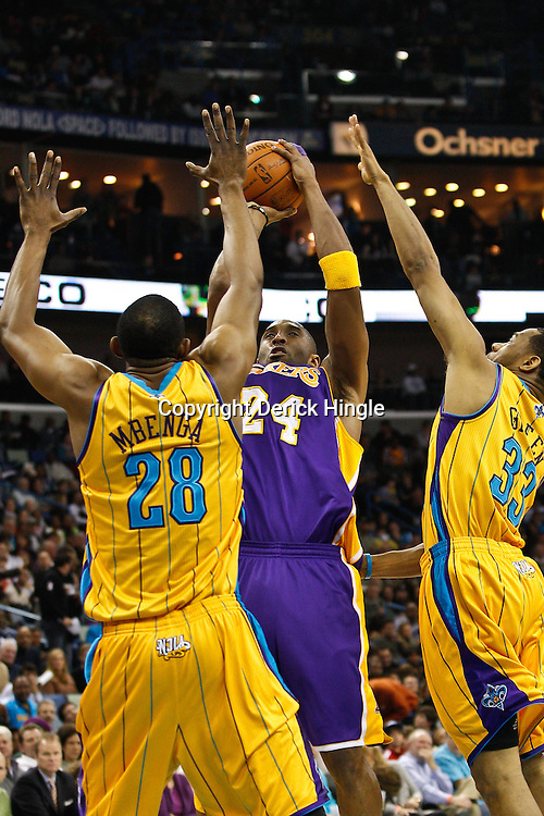 February 5, 2011; New Orleans, LA, USA; Los Angeles Lakers shooting guard Kobe Bryant (24) shoots over New Orleans Hornets center D.J. Mbenga (28) and shooting guard Willie Green (33) during the first quarter at the New Orleans Arena.   Mandatory Credit: Derick E. Hingle
