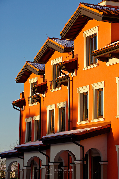 "Architectural details of residential real estate development project ""Italian Village"" in Kyiv, Ukraine. Exterior view of townhouses with red walls in the sunset sunlight."