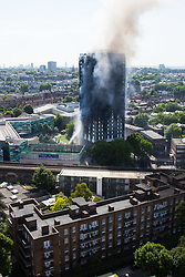 London, June 14th 2017. A fire rages through a residential tower block, Grenfell Tower, in Kensington, West London, with the entire building engulfed in flames. More than 200 firefighters are attending the incident and there are reports of people trapped inside. No figures are available as to casualties. Most of the upper floors are still ablaze.