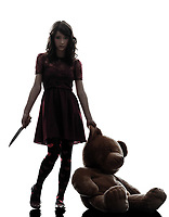 one  strange young woman killer holding bloody knife an teddy bear in silhouette white background