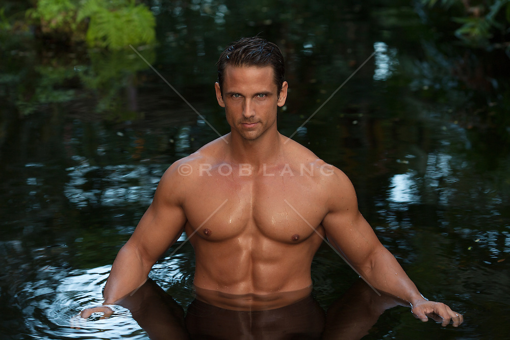 good looking man without clothes standing in a small pond in Florida