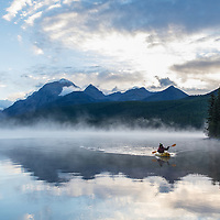 A kayaker paddles back in towards the shore after a sunrise trip on Bowman Lake in the Glacier National Park.