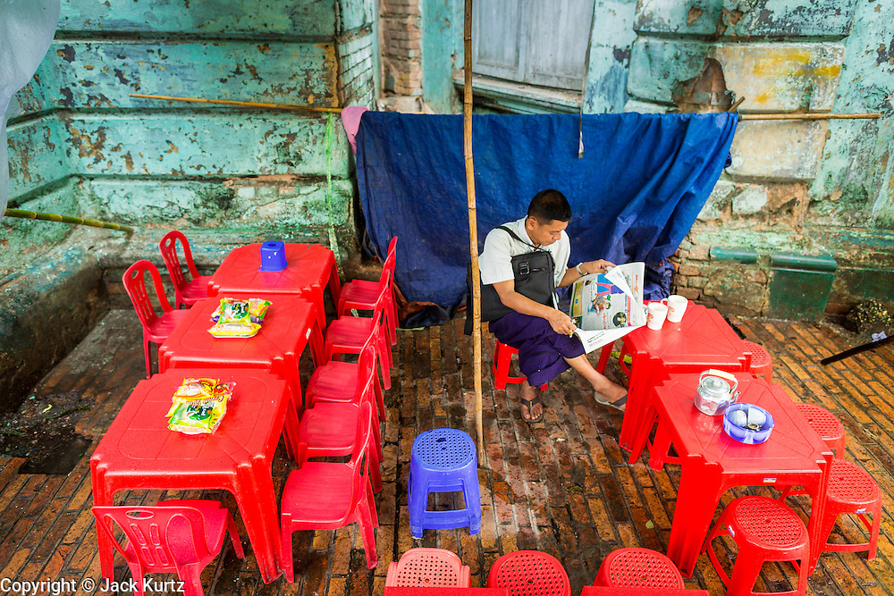 12 JUNE 2013 - YANGON, MYANMAR: A man reads a Burmese newspaper in a Yangon teahouse.         PHOTO BY JACK KURTZ