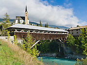 "Walk across a covered wooden bridge in Scuol (or Schuls, 1244 meters or 4081 feet elevation), in Graubünden canton, Lower Engadine, Grison Alps, Switzerland, Europe. Scuol is the terminal station of the ""Rätische Bahn"" (RhB). The Swiss valley of Engadine translates as the ""garden of the En (or Inn) River"" (Engadin in German, Engiadina in Romansh, Engadina in Italian)."