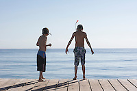 Two boys (7-11) on jetty wearing snorkelling masks back view