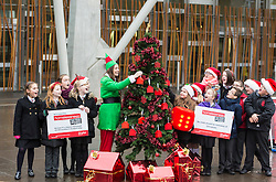 "Campaigners from Shelter Scotland raise awareness of their campaign ""Homelessness - Far From Fixed"" outside the Scottish Parliament in Edinburgh. They are joined by carol singers from Corstorphine Primary School, a Christmas tree and a giant snakes and ladders board game - Chance Not Choice - which illustrates how life chances affect people's ability to keep a roof over their head."
