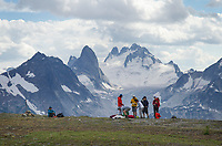 Group of heli-hikers on Rocky Point Ridge. Howser Towers, Vowell Glacier in the distance. Bugaboo Provincial Park Purcell Mountains British Columbia.