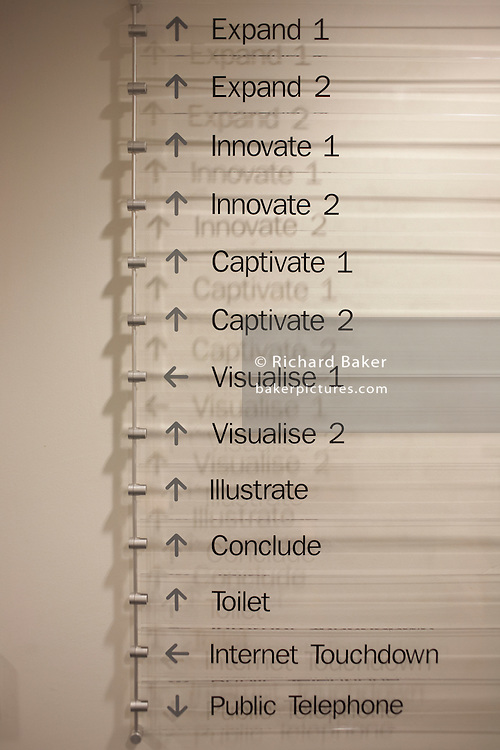 A menu of seminar room choices is placed near an entrance for those attending a counselling workshop held for employees at Prospect House, Borough, Southwark, London. Words like 'Visualise, Captivate, Innovate and Expand' are listed vertically on a perspex board as well as directions to amenities such as the toilet and an 'Internet Touchdown.' Soon, seminar participants will arrive for a day's role-playing and brainstorming in classrooms named after these concepts. Encouraging the students to be inspired by these verbs.