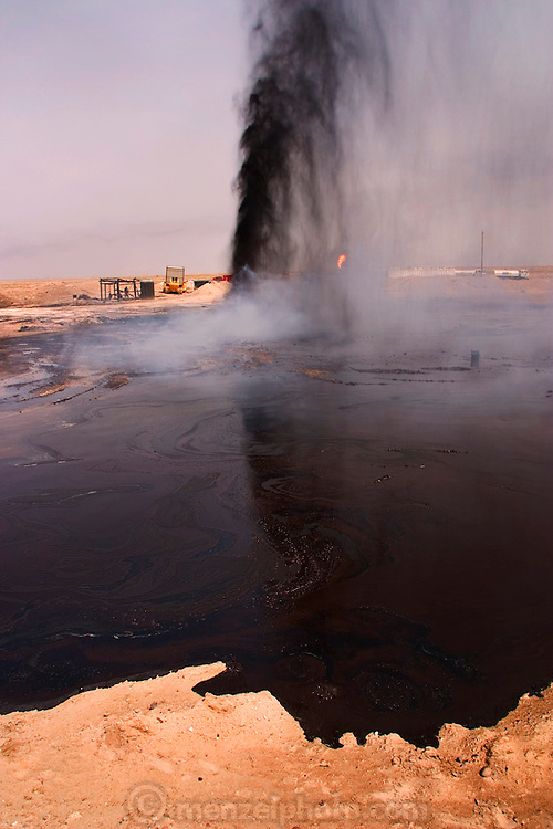 "An oil well gusher in southern Iraq's Rumaila oil field.  Gushers are capped by using a ""stinger,"" a tapered pipe on the end of a long steel boom controlled by a bulldozer. Drilling mud, under high pressure, is pumped through the stinger into the well, stopping the flow of oil and gas. The Rumaila field is one of Iraq's biggest oil fields with five billion barrels in reserve. Rumaila is also spelled Rumeilah."