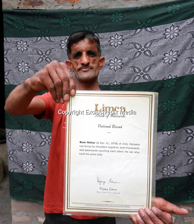 'Rubber Man' smashes bizarre record by breaking CDs between his shoulders - in front of his chest<br /> <br /> Farmers aren't renowned for being particularly supple.<br /> But Rammehar Punia has bucked the trend with record-breaking results.<br /> The 35-year-old has been dubbed 'Rubber Man' thanks to his remarkable ability to make his shoulders meet in front of his chest. <br /> <br /> And he has used this flexibility to smash the Guinness World Record for the number of CDs broken between the shoulders – 60 in just one minute.<br /> <br /> His suppleness also allows him to wrap his left hand around his neck so far that he can grab hold of his left ear.<br /> Mr Punia set himself the challenge of breaking records when he was at school and began training his body to reach the extreme limits he achieves today. <br /> <br /> He broke his first Guinness World Record in 2011 when he cracked 41 CDs in a minute.<br /> <br /> This was later beaten, but he went on to win it back by breaking 60 in as many seconds after training for up to four hours a day while holding down his job as a farmer.<br /> <br /> Mr Punia, from Panipat, India, has performed shows in various cities across his homeland and abroad, including in Italy. <br /> ©Exclusivepix Media