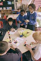 Primary school children using unilink blocks and number fans in practical maths lesson,