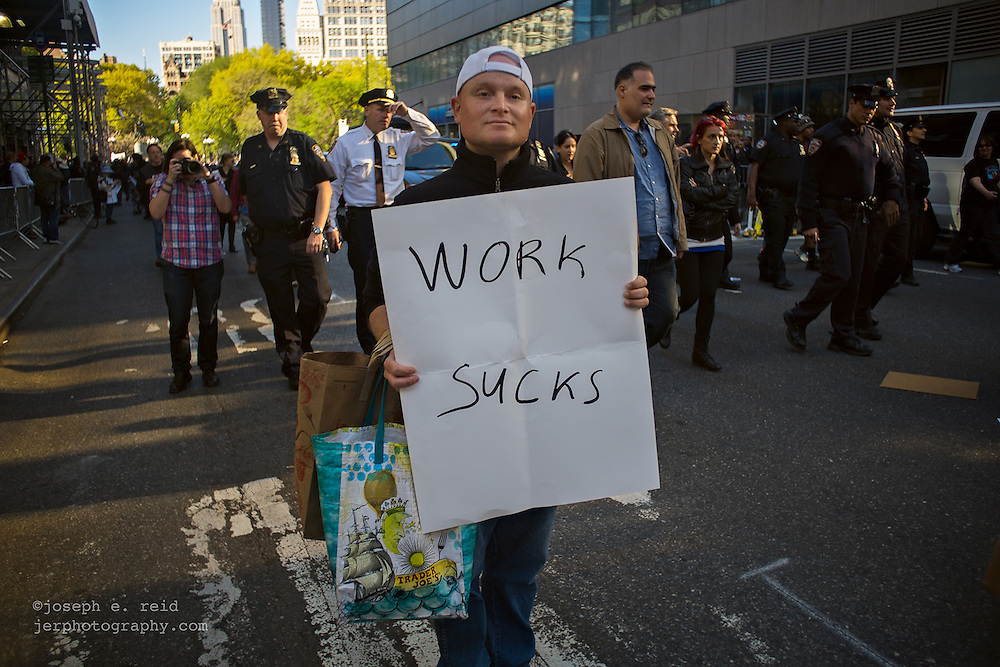 """A man with a sign reading """"work sucks"""" was among the crowd of workers' rights demonstrators who marched down Broadway towards City Hall after a rally in New York's Union Square to mark  International Workers' Day, also known as May Day."""