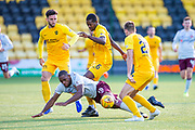 Uche Ikpeazu (#19) of Heart of Midlothian FC is pushed to the ground by Jon Guthrie (#27) of Livingston FC and Marvin Bartley (#6) of Livingston FC during the Ladbrokes Scottish Premiership match between Livingston FC and Heart of Midlothian at the Tony Macaroni Arena, Livingston, Scotland on 26 October 2019.