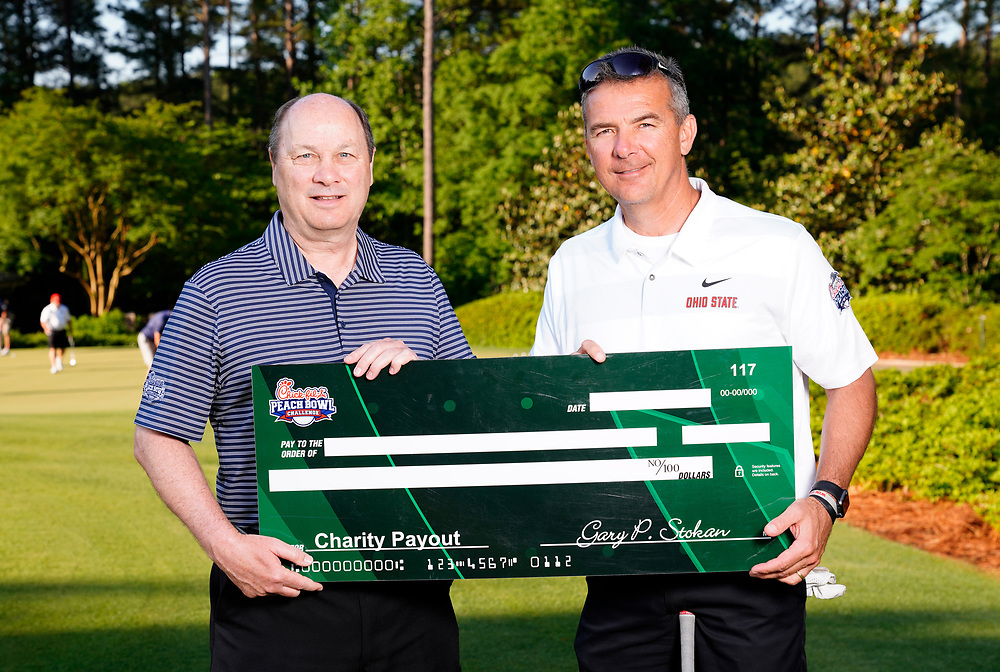 Peach Bowl, Inc. CEO & President Gary Stokan presents Former Ohio State head football coach Urban Myer a check for his charity after the Chick-fil-A Peach Bowl Challenge at the Ritz Carlton Reynolds, Lake Oconee, on Tuesday, April 30, 2019, in Greensboro, GA. (Paul Abell via Abell Images for Chick-fil-A Peach Bowl Challenge)